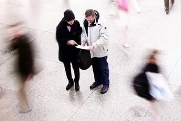 Titelbild für das Menü Vielfalt leben mit zwei Menschen in einer belebten Halle, die zusammen auf einen Plan schauen. Bibelvers: Gott, zeige mir deine Wege und lehre mich deine Steige. Psalm 25,4